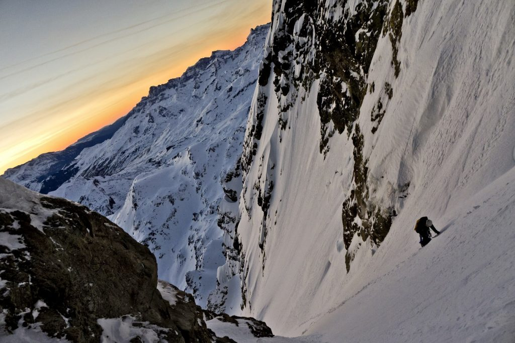 single climber on side of steep mountain at sunset