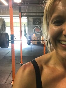 woman in black tank top in front of barbell at gym