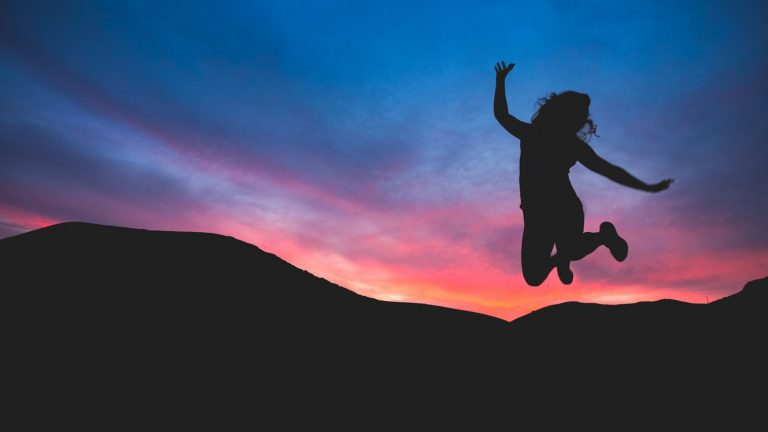 Silhouette of a woman jumping in front of mountains and sunset