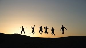 silhouettes of six people jumping near mountain at sunset