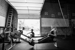 woman and boy rowing on rowing machines in gym with open garage door