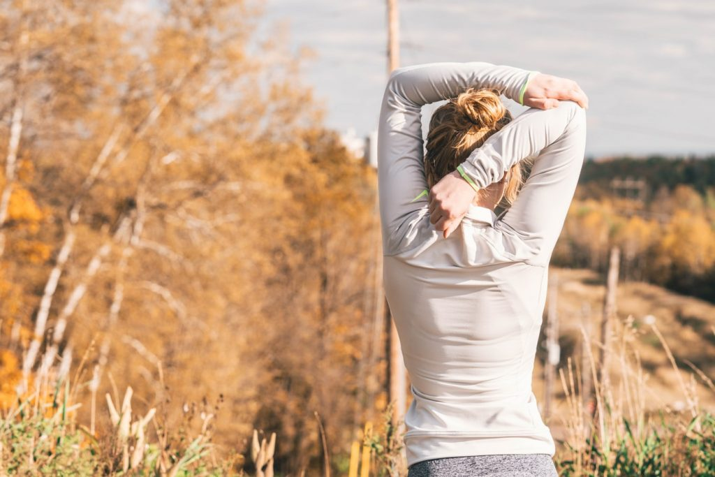woman in exercise clothes stretching in morning sun