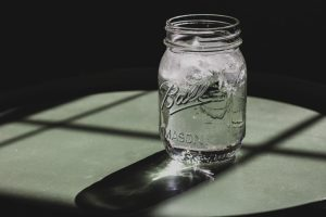 iced water in a glass mason jar on table