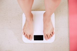 woman's feet standing on white bathroom scale