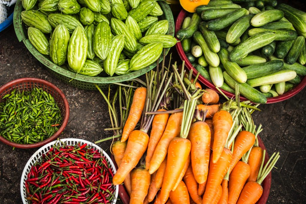 carrots and other vegetables in containers on dark background